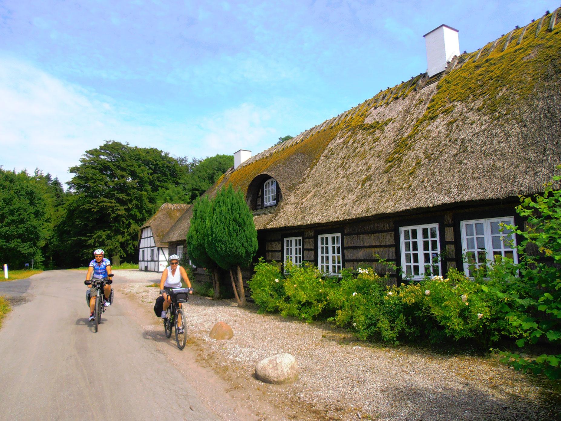 Donne in bicicletta in strada vicino a una casa
